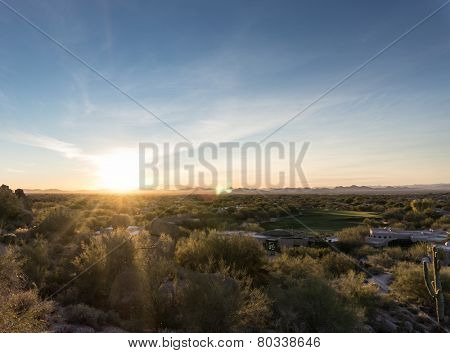 Lens flares from dipping sun illuminate upscale Scottsdale golf community area