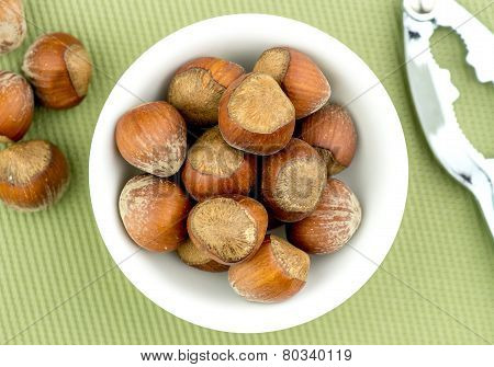Natural Hazelnuts In Bowl With Nut Cracker Aerial