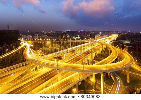 skyline and traffic trails on highway intersection at night