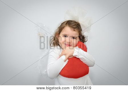 Young girl holding a plush red heart