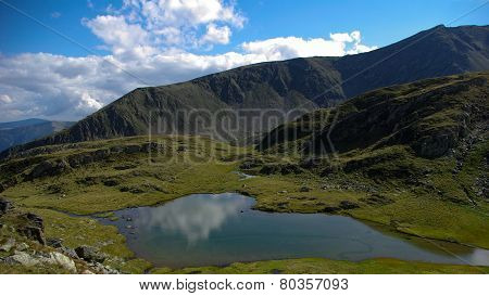 Mountain landscape with lake and clouds in the sky