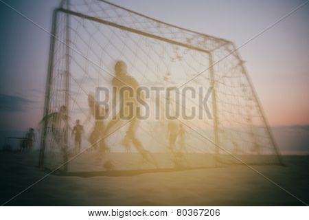 Boys Playing Football On The Beach In Summer