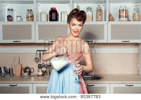 The Girl Pours Milk From A Jug.