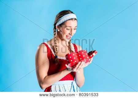 Woman in dirndl dress opening gift or present