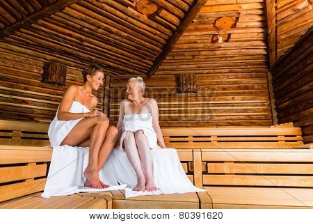 Senior and young woman in sauna sweating in heat