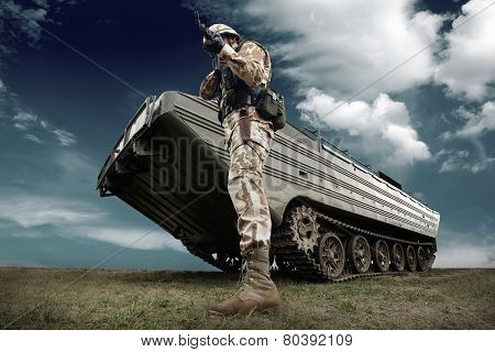 Military tank and soldier outdoors.