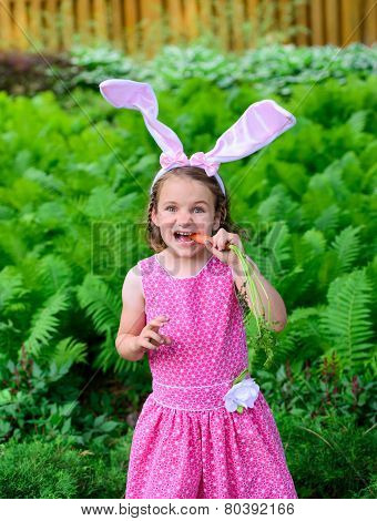 Little Girl Wearing Bunny Ears Eating A Carrot