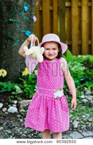 Little Girl Holding A Purse With An Easter Bunny