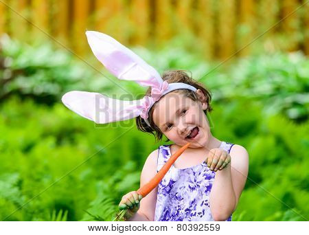Young Girl In Bunny Ears Holding A Carrot