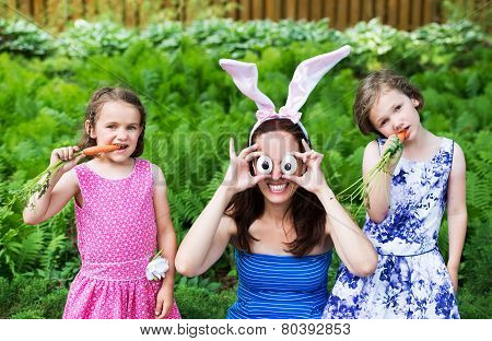 Mother Wearing Bunny Ears And Silly Eyes Poses With Children