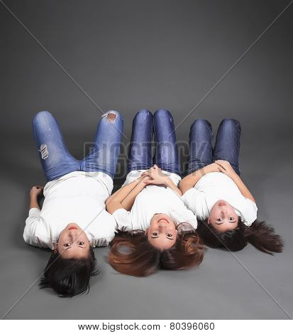 Three sisters lying on the floor in jeans