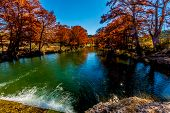 foto of guadalupe  - Beautiful Fiery Fall Foliage on the Emerald Colored Guadalupe River, Texas.