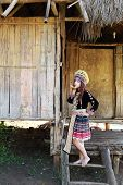 stock photo of hmong  - Traditionally dressed Mhong hill tribe woman in the wooden cottage
