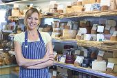 image of deli  - Owner Of Delicatessen Standing Next To Cheese Display - JPG