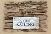 stock photo of driftwood  - Gone sailing old weathered sign on driftwood and beach sand background - JPG