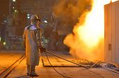 foto of furnace  - Smelting furnace with detail of a worker