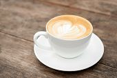 stock photo of latte  - cup of coffee latte art heart on wood - JPG