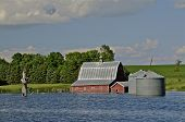 picture of flood  - An expanding lake has flooded over the building site of the grain tanks and barn - JPG