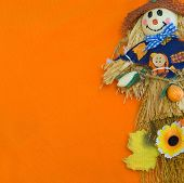 image of scarecrow  - Close up of a smiling Halloween scarecrow on orange background - JPG