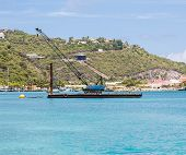 stock photo of barge  - A blue crane on a working barge over blue water in the harbor of Philipsburg in St Martin - JPG