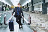 picture of carry-on luggage  - Portrait of male entrepreneur in business suit smiling at the camera while carrying luggage and briefcase in the airport hall - JPG