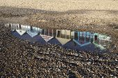 foto of beach hut  - Reflections of beach huts in a puddle on Southwold beach Suffolk England - JPG