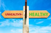 picture of unhealthy lifestyle  - Wooden signpost with two opposite arrows over clear blue sky Healthy versus Unhealthy messages Healthy Lifestyle conceptual image - JPG