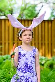 pic of bunny ears  - A young girl wearing Easter bunny ears holds a fresh carrot in her hand while posing like a bunny outside in a lush garden setting during the spring season - JPG