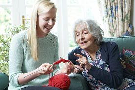 stock photo of grandmother  - Grandmother Showing Granddaughter How To Knit At Home - JPG