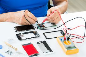 pic of electricity meter  - Close-up Of Man Repairing Cellphone With Multimeter ** Note: Shallow depth of field - JPG