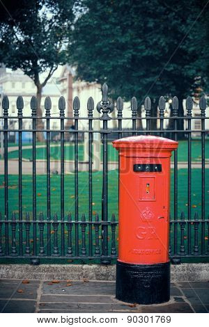 Red post box in street with historical architecture in London.