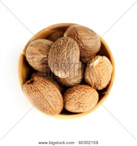 Nutmeg in wooden bowl, isolated on white