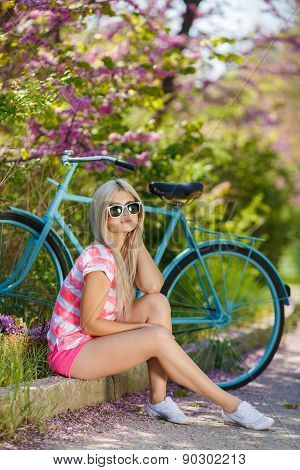 Young woman resting in the Park after a day of Cycling.