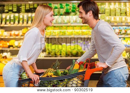 Young couple leaning over the shopping cart