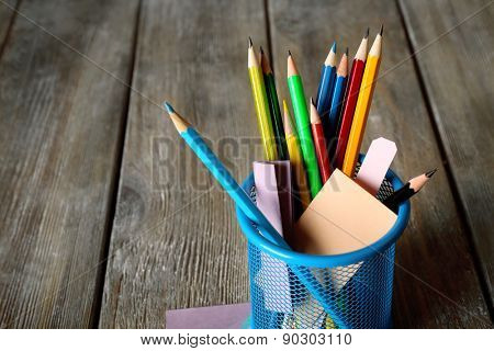 Colorful pencils in metal holder with sticky notes on wooden planks background
