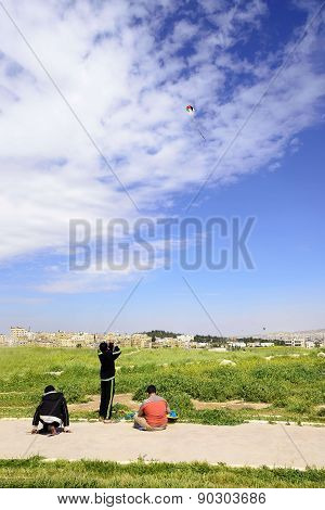 View of three jordanian boys playing with kite in Amman Citadel, Jordan