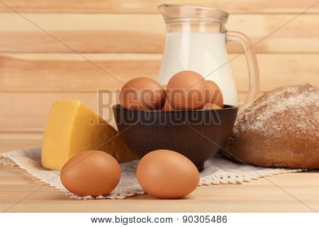 Eggs in clay bowl, milk in glass jug, cheese and loaf of bread on wooden planks background