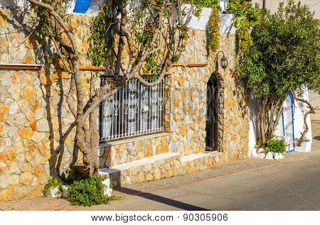 Stone facade and ivy on Greek street, Greece