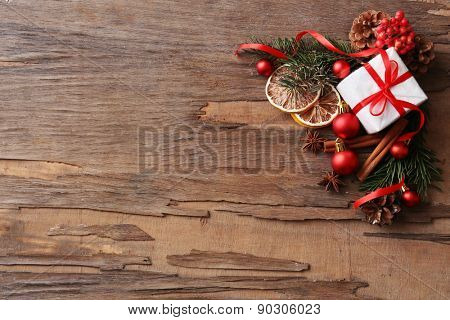 Slices of dried lemon with present box, baubles and sprig of Christmas tree on rustic wooden background