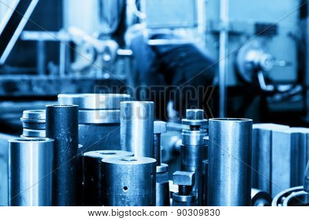 Industrial steel cylinders, pistons in workshop. Machine working in the background. Industry theme.