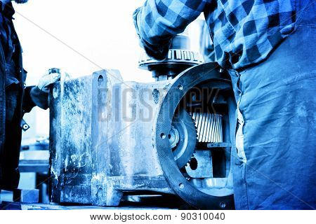 Workers repair, work on old gear element in workshop. Industry, industrial concept.
