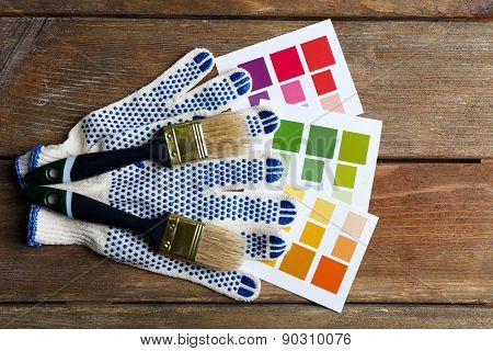 Color samples, gloves and paintbrushes on wooden table background