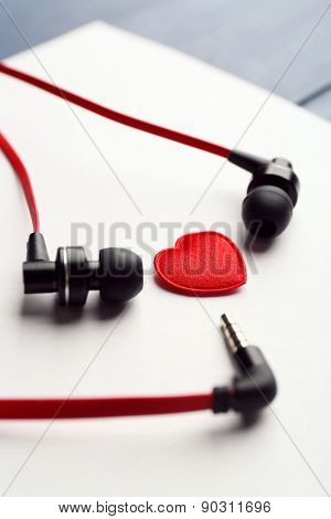 Earphones on white sheet of paper with small heart, closeup