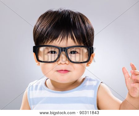 Cute baby boy with black glasses and hand raised up