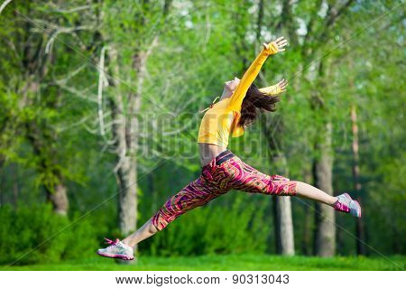 Young beautiful girl doing gymnastic jumps outdoors