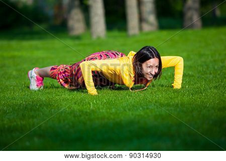press ups exercise by young woman. Girl working out on grass crossfit strength training in the glow