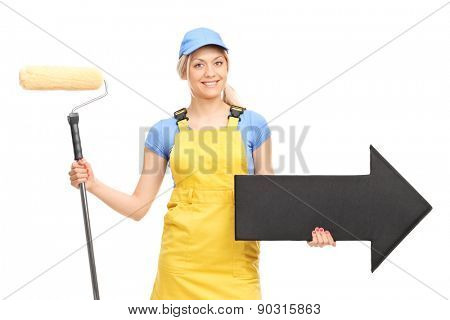 Female painter in a yellow uniform holding a paint roller and a big black arrow pointing right isolated on white background