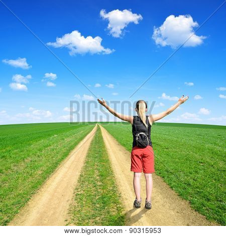Girl standing on a meadow trail