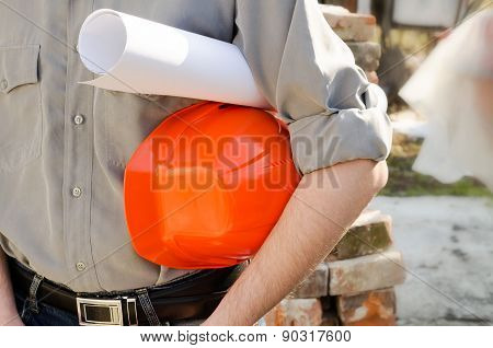 Man Holds A Protective Construction Helmet And The Project In Hand