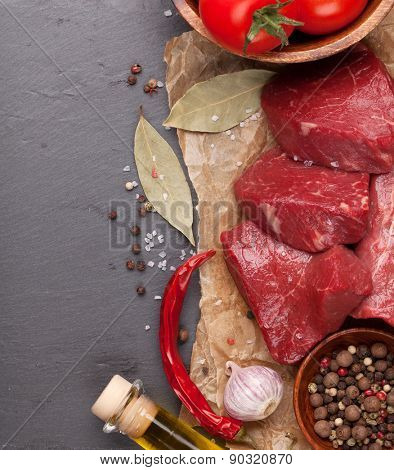 Raw fillet beef steak and spices on stone board. Top view with copy space